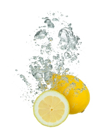 Isolated shot of lemon falling into water, isolated on white backgroundの写真素材