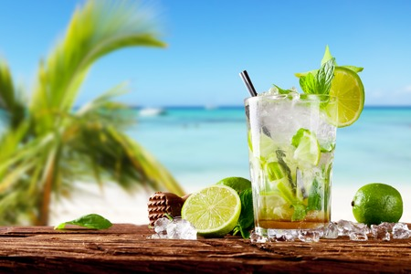Photo pour Mojito drink on wood with blur beach background - image libre de droit