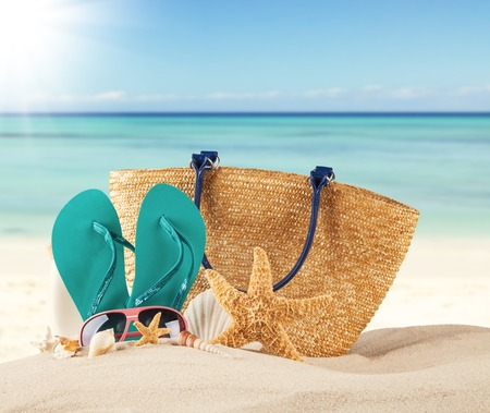Photo pour Summer concept with sandy beach, shells and blue sandals - image libre de droit