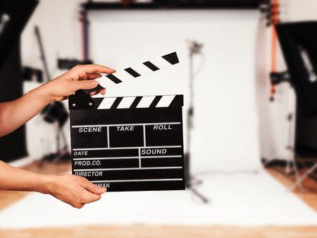 Man hands holding film clapper. Blur film studio on background