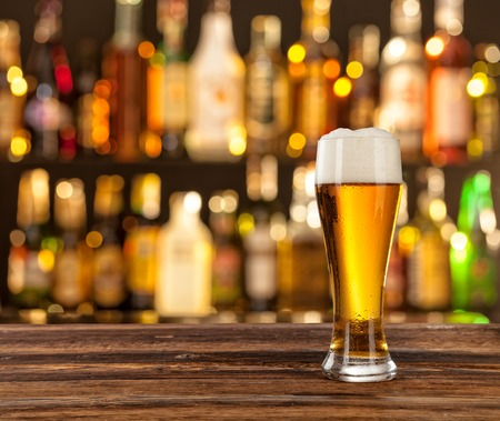 Photo pour Glass of light beer served on wooden desk. Bar on background - image libre de droit