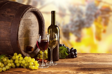 Photo pour Red and white wine bottle and glass on wooden keg. Grapes of wine on background - image libre de droit