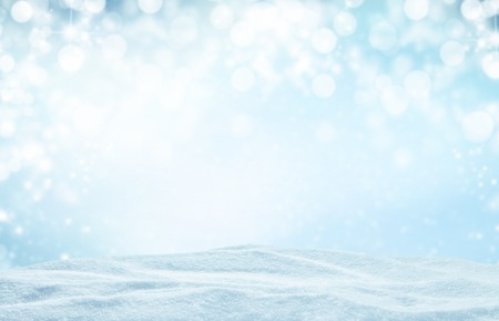 Winter background with pile of snow and blur abstract lights. Copyspace for text