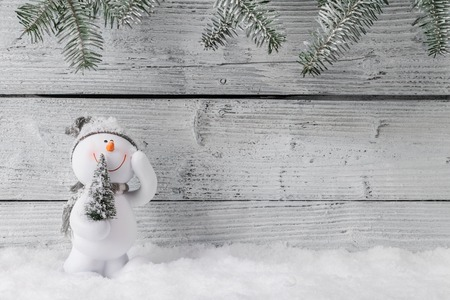 Christmas still life decoration with snowman on wooden background.