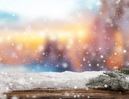 Winter background with pile of snow and blur evening landscape. Empty wooden planks on foreground. Copyspace for text