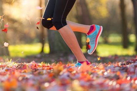 Close up of feet of female runner running in autumn leaves. Fitness exercise, low depth of focus