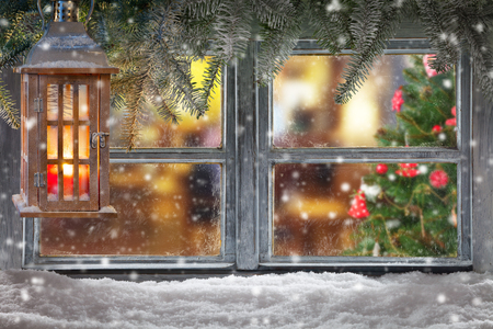 Atmospheric Christmas window sill decoration with home cozy interior. Christmas tree on background