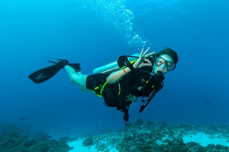 Photo for Young female scuba diver underwater showing ok signal - Royalty Free Image