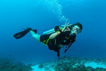 Photo pour Young female scuba diver underwater showing ok signal - image libre de droit