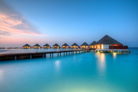 Foto de Water villas in lagon, Maldives resort island in sunset - Imagen libre de derechos