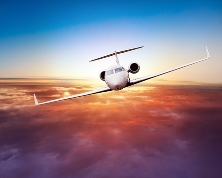 Photo pour Private jet plane flying above clouds in beautiful sunset. Shot from front view - image libre de droit