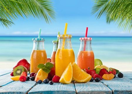 Foto de Fresh glasses of juice with fruit mix placed on the beach on wooden planks. Concept of healthy drinks, antioxidants and summer cocktails. - Imagen libre de derechos