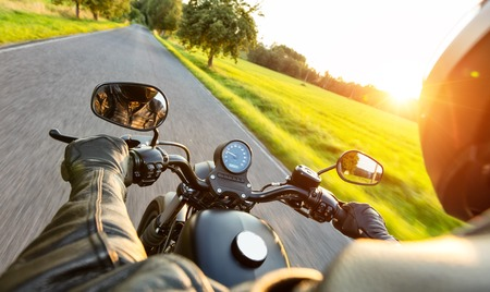 Photo for Motorcycle driver riding on motorway in beautiful sunset light. Shot from pillion driver view - Royalty Free Image