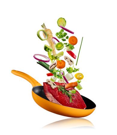 Foto de Fresh vegetables with steak flying into a pan, isolated on white background - Imagen libre de derechos