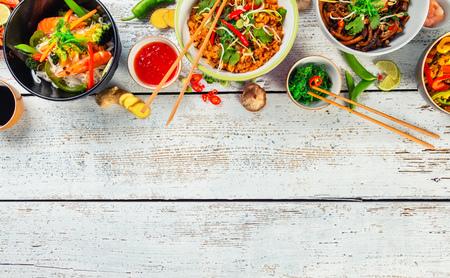 Foto de Asian food served on white wooden table, top view, space for text. Chinese and vietnamese cuisine set. - Imagen libre de derechos