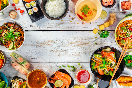 Foto de Asian food served on white wooden table, top view, space for text. Chinese and vietnamese cuisine set. - Imagen libre de derechos