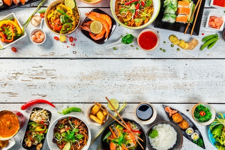 Asian food served on white wooden table, top view, space for text. Chinese and vietnamese cuisine set.