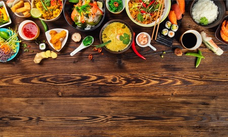 Foto de Asian food served on old wooden table, top view, space for text. Chinese and vietnamese cuisine set. - Imagen libre de derechos