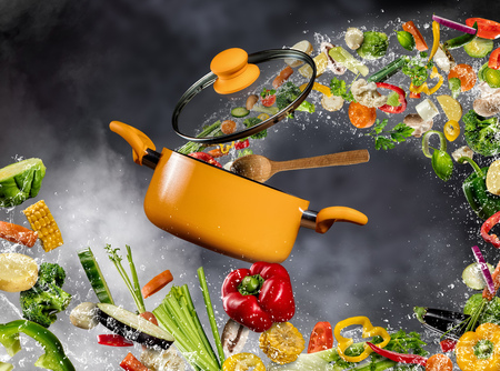 Photo for Fresh vegetable in water splash flying into a pot with wooden spoon, separated on dark background. Concept of food preparation and cooking - Royalty Free Image