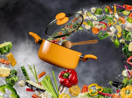 Foto de Fresh vegetable in water splash flying into a pot with wooden spoon, separated on dark background. Concept of food preparation and cooking - Imagen libre de derechos