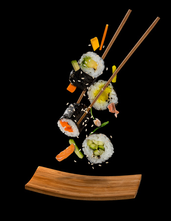 Photo pour Sushi pieces placed between chopsticks, separated on black background. Popular sushi food. Very high resolution image - image libre de droit