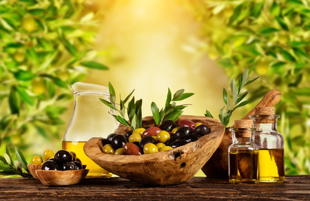 Photo for Freshly harvested olives berries in wood bowls and pressed oil in glass bottles. Still life of food preparation served on old wooden planks. Free space for text. Very high resolution of image - Royalty Free Image