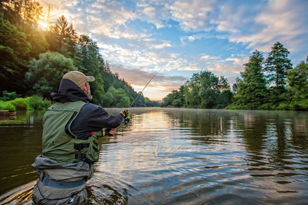 Photo pour Sport fisherman hunting predator fish. Outdoor fishing in river during sunrise. Hunting and hobby sport. - image libre de droit