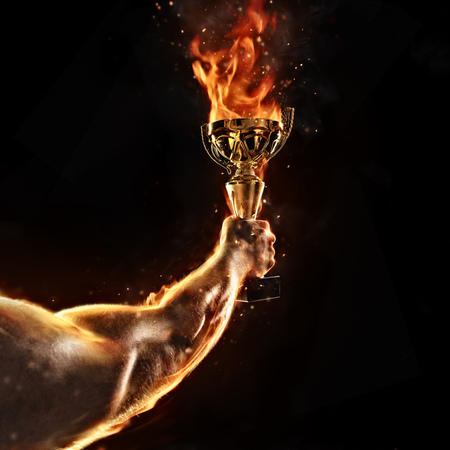 Photo pour Muscular man arm holding burning trophy cup on black background. Detail of fighter hand. Concept of success, hard work and conquest of the target. High resolution - image libre de droit