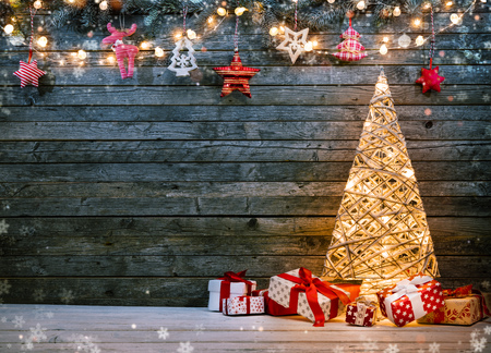 Holidays background with illuminated Christmas tree, gifts and decoration. Dark wooden background with free space for text. Celebration of christmas