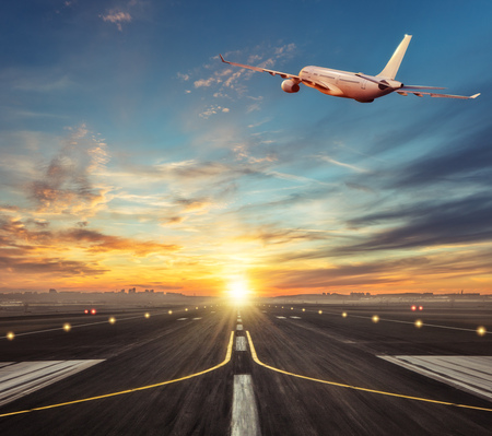 Photo pour Commercial airplane flying above runway in sunset light. Travel and business theme. - image libre de droit