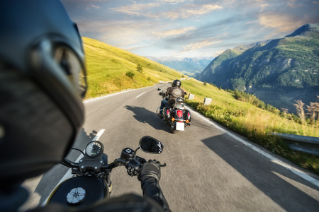 POV of motorbiker holding steering bar, riding in Alps in beautiful sunset dramatic sky. Travel and freedom, outdoor activities