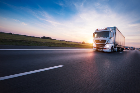 Photo for Loaded European truck on motorway in beautiful sunset light. On the road transportation and cargo. - Royalty Free Image