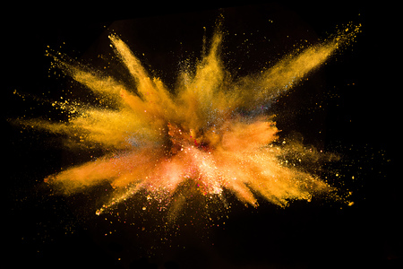 Foto de Explosion of colored powder isolated on black background. Abstract colored background - Imagen libre de derechos