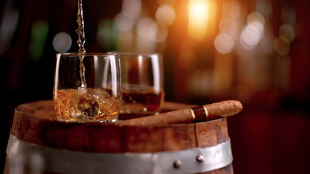 Photo pour Pouring whiskey into glass. Placed on wooden keg. Low depth of focus - image libre de droit