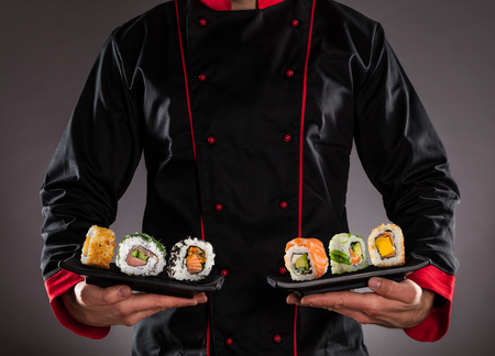 Photo pour Closeup of master chef holding plates with sushi pieces. Concept of asian food - image libre de droit