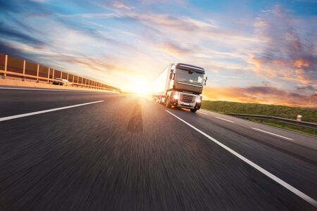 European truck vehicle on motorway with dramatic sunset light. Cargo transportation and supply theme.