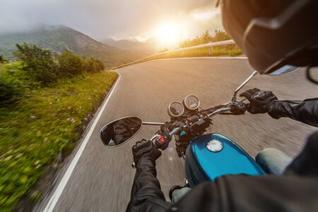View from motorcycle driver perspective riding in Alpine landscape during sunrise