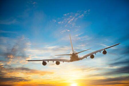 Photo pour Passengers commercial airplane flying in sunset light. - image libre de droit