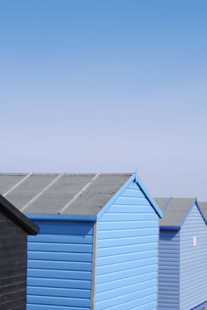 Blue beach huts with a bright blue sky, portrait format