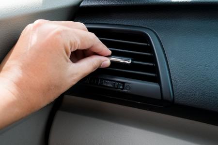 hand adjusting air conditioner in car
