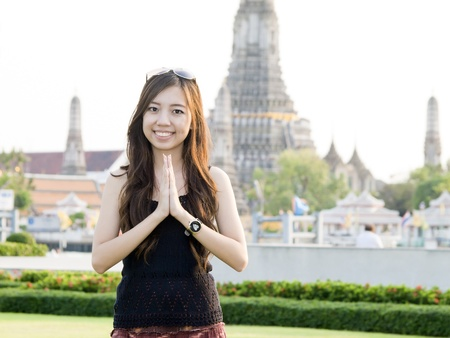 Attractive asian woman greeting with Temple of Dawn Wat Arun background