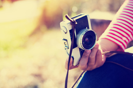 Vintage young hipster girl photographer hand holding retro camera