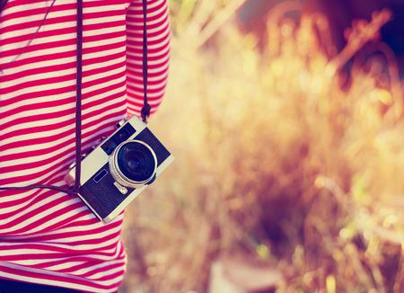 Foto de Vintage young hipster girl photographer with retro camera in holiday travel - Imagen libre de derechos