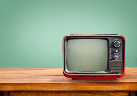 Retro red television on wood table with vintage aquamarine wall background