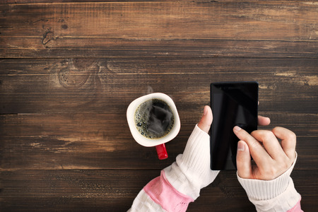 Above view of female hand holding smart phone with hot cup of coffee on wood table