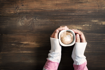 Above view of female hand holding hot cup of coffee on wood table