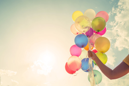 Foto de Girl hand holding multicolored balloons done with a retro vintage instagram filter effect, concept of happy birthday in summer and wedding honeymoon party (Vintage color tone) - Imagen libre de derechos