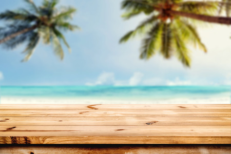 Foto de Top of wood table with blurred sea and coconut tree background - Empty ready for your product display montage. Concept of beach in summer - Imagen libre de derechos