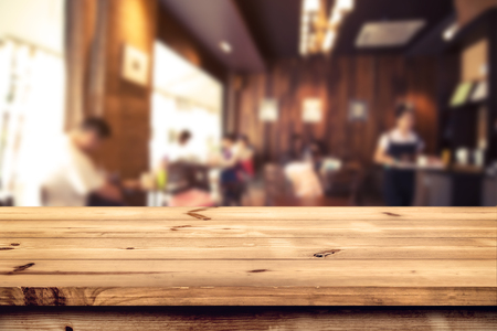 Top of wood table counter with blurred coffee shop (cafe) and restaurant shop interior background - Empty table ready for your product display or montage. vintage effect tone