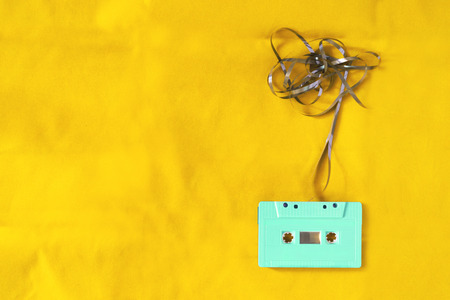 Top view of cassette tape over yellow background with tangled ribbon. retro filter effect and vintage style